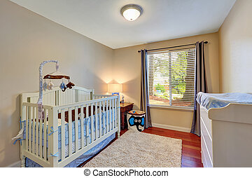 Cozy nursery room with white wooden crib.