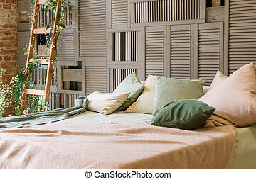 Cozy pastel colors bedroom with brown wooden wall and simple wooden furniture in minimalist style. the pillows on the bed are pink and green. decorative ladder decorated with flowers