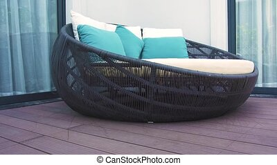 Cozy rattan sofa with cushions in lounge area on summer...