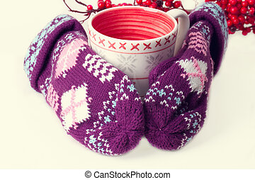 Cozy red gloves hold a mug of hot cocoa