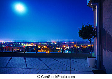 cozy rooftop patio area in the moonlight with night city view