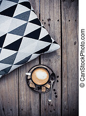 cup of coffee and pillow on wooden floor