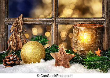 Christmas, Advent or winter seasonal arrangement on a window sill, decorated with snow, with cozy candle light, ornaments and fir branches