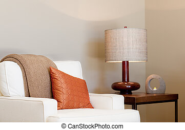 cozy seat with throw and pillow, lamp and burning candle in...