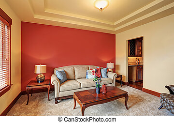 Cozy sitting room with antique beige sofa and red wall...