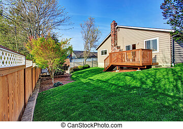 Cozy small backyard with wooden walkout deck