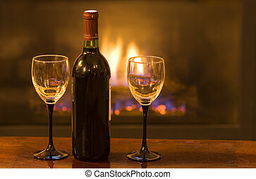 Bottle of wine with two empty glasses infront of a warm fire