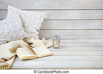 Cozy still life with lantern, pillows, book and plaid