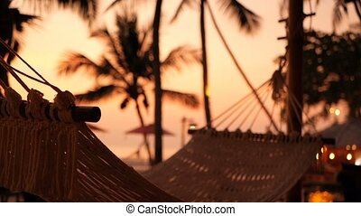 Cozy white hammock on the beach against a background of the swimming pool, ocean and sunset.