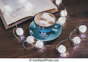 Cozy winter home. Cup of cocoa with marshmallows, open book, Christmas garland, on a wooden table. Kind atmosphere of evening reading.