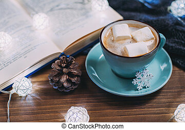Cozy winter home. Cup of cocoa with marshmallows, warm knitted sweater, open book, Christmas garland, pune cone on a wooden table. Atmosphere of a pleasant reading.
