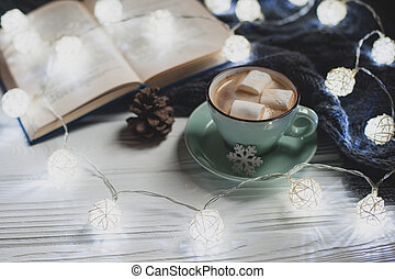 Cozy winter home. Cup of cocoa with marshmallows, warm knitted sweater, open book, Christmas garland, lump on a white wooden table. Atmosphere of a pleasant evening for reading.