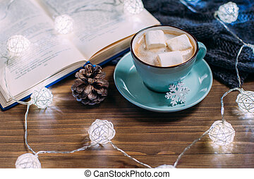 Cozy winter home. Cup of cocoa with marshmallows, warm knitted sweater, open book, Christmas garland on a white wooden table. Atmosphere of a pleasant evening for reading.