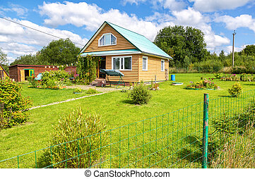 Cozy wooden country house with outbuildings