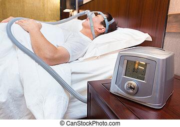 cpap, máquina, sentado, en, un, tabla de cabecera, con, confuso, edad media, hombre asiático, sueño, en, el suyo, cama, llevando, cpap, máscara, en, el, plano de fondo