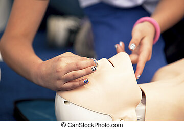 CPR training - First aid training. Demonstrating CPR on a...