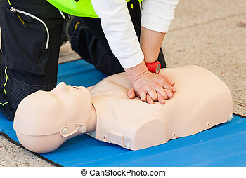CPR training with dummy - Female instructor showing CPR on...