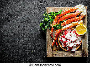 Crab meat and sea crab on tray with lemon and parsley.