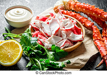 Crab meat on a plate with sauce, lemon and parsley.