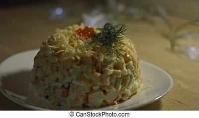 Crab salad on a plate decorated with grated cheese, dill and red salmon caviar. Salad of crab sticks, cheese, cucumber, canned corn, mayonaisse and eggs in the kitchen at home. Artistic shooting.