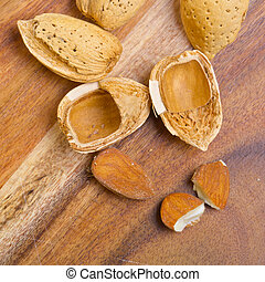 Cracked almond kernel with shells on wooden background