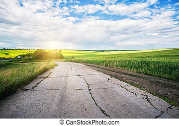 Cracked asphalt road to the sun in the field