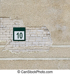 brick wall and plate with a number ten