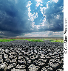 cracked earth under stormy clouds. global warming