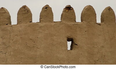 Cracked merlons on a clay wall in Uzbekistan - A close-up...