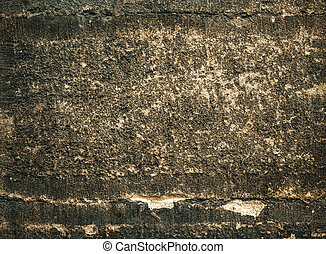 Cracked old stone wall background, dark grunge texture close up