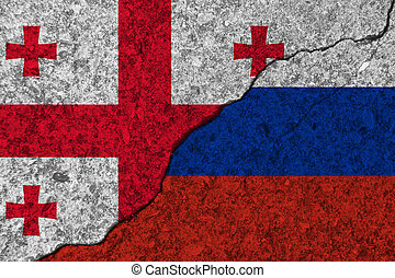 Cracked painted concrete walls between the Georgia flag and Russia. Concept of conflict.