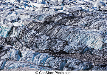Cracked pattern of the glacier surface with deposits of black volcanic cinder, cyan blue icy reflects are at interior walls of cracks