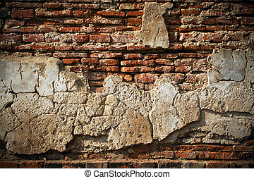 Cracked plaster of the wall to see the old brick inside