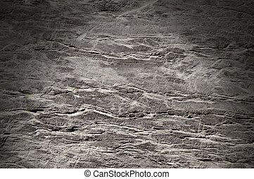 Cracked rock surface texture lit dramatically from above