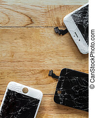 Cracked smartphone screen on wooden background