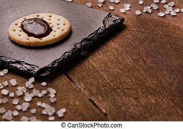 cracker, met, jam, op bovenkant, op, black , steen, grof, suiker, op, houten, achtergrond., de ruimte van het exemplaar