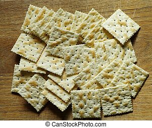 CRACKERS - A selection of soda crackers against a wood...