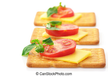 Crackers with cheese, tomato and basil