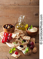 crackers with soft cheese olives grapes. healthy appetizer