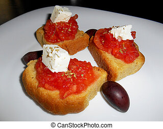 Crackers with tomato, olives, orega