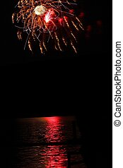 crackling fireworks with lake reflection