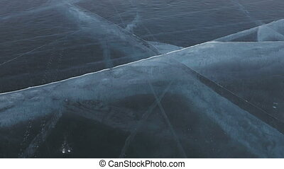 Cracks in transparent ice. Beautiful winter Lake Baikal.