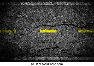 Cracks on asphalt the yellow line dividing lanes