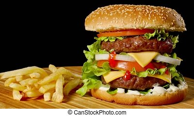 Craft beef burger and french fries on wooden table isolated...