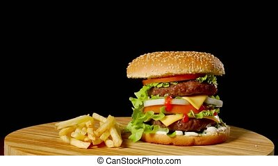Craft beef burger and french fries, sauce isolated on black...