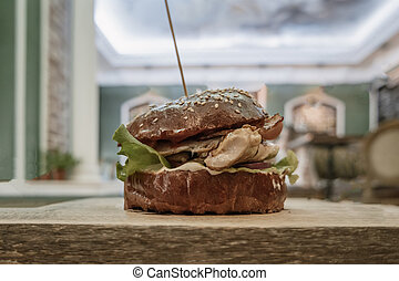 Craft beef burger on wooden table side view