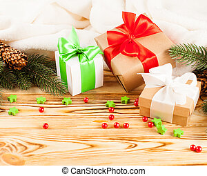Craft gift boxes with color ribbon and bow, green Christmas tree, decorations, white plaid on wooden background. Xmas and New Year congratulation card, banner, flyer.