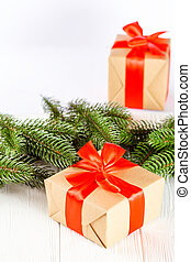 Craft gift boxes with red ribbon and bow, green Christmas tree, decorations, on white wooden background. Xmas and New Year congratulation card, banner, flyer.