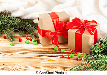 Craft gift boxes with red ribbon and bow, green Christmas tree, decorations, white plaid on wooden background. Xmas and New Year congratulation card, banner, flyer.