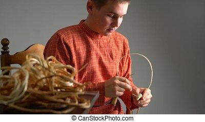 Crafts. View of boy weaves basket in studio